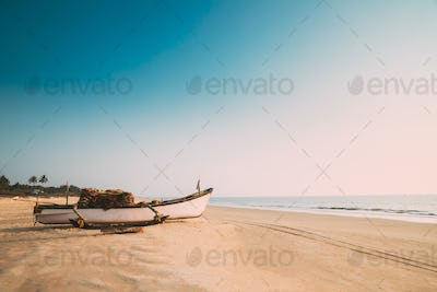 Goa, India. Old Wooden Fishing Boat Standing On Sea Ocean Beach. Tropical Palms On Background