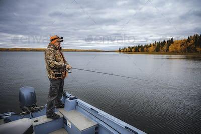 A man fishing at the lake. Fishing from a boat autumn season.