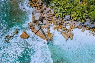 Anse Cocos beach tropical island La Digue Seychelles. Drone aerial view of foam ocean waves rolling
