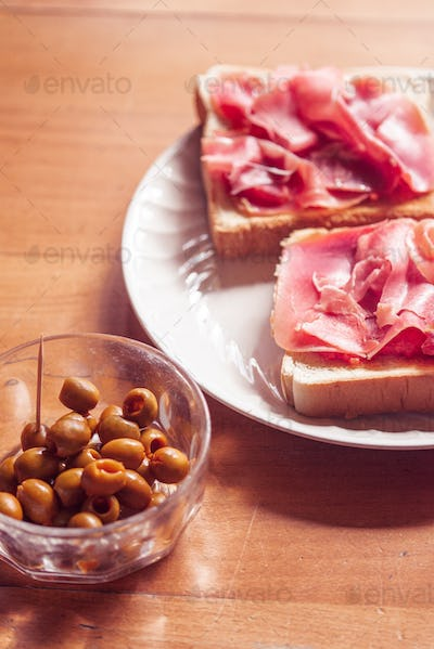 Green olives and toast with serrano ham, traditional spanish snack