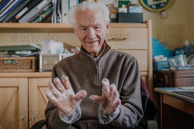 Elderly man puts on disposable protective gloves