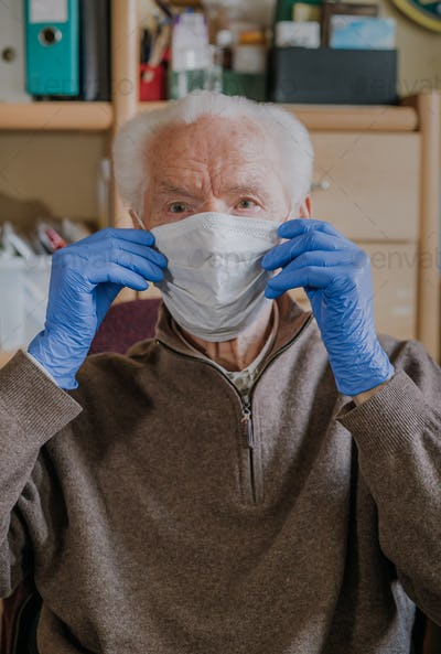 Old man wearing protective mask and gloves