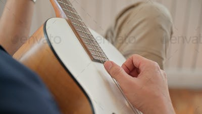 Young man playing guitar at home He stopped at home because of the virus outbreak.