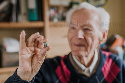 Old man holding one green tablet in hand closeup
