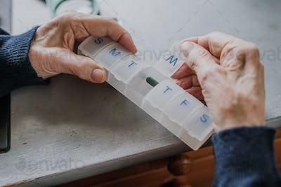 Senior arranges medicines for each day of week