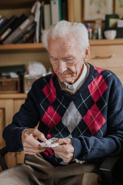 Old man holding medicine blister in hands