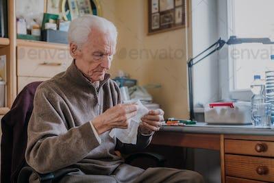 Senior preparing dressing, cuts gauze