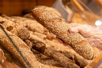Gloved hand of mature female customer taking fresh bread with sesame sprinkles