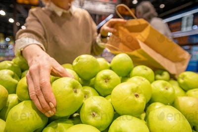 Hand of aged woman with paperbag taking fresh granny smith apple