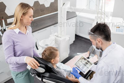 Young contemporary dentist showing dental x-ray in tablet to his little patient