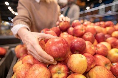 Hand of mature female customer choosing fresh red apples on fruit display