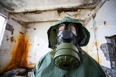Dramatic portrait of a man wearing a gas mask in a ruined building.