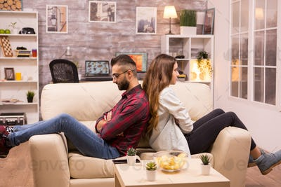Couple sitting back to back on the couch ignoring each other