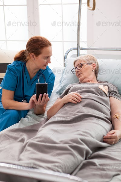 Female caretaker in nursing home talking with old woman
