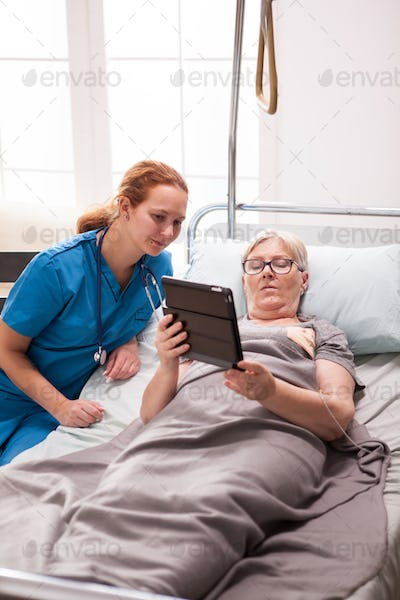 Young doctor and senior woman in nursing home