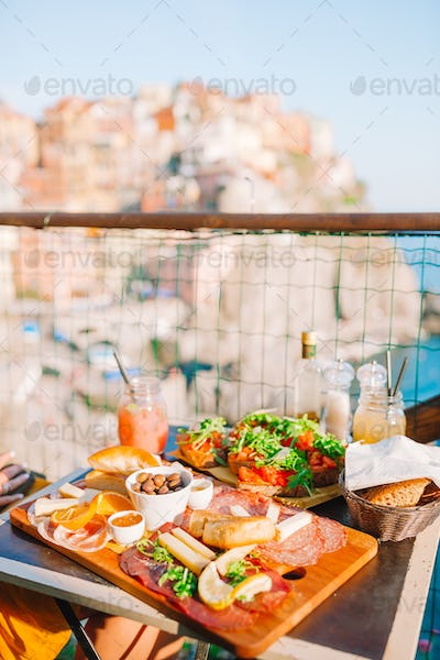 Fresh bruschettes, cheeses and meat on the board in outdoor cafe with amazing view in Manarola
