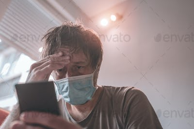 Worried man using mobile phone in home quarantine self-isolation