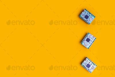 three microcircuit over orange background minimal engineering concept