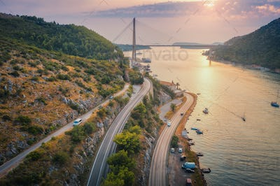 Aerial view of mountain roads  and beautiful bridge at sunset
