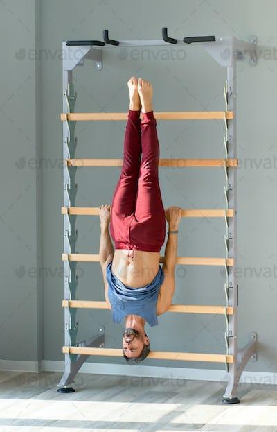 Athletic man exercising on a gymnastics ladder