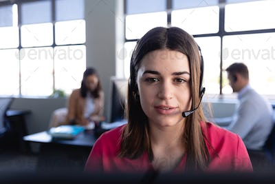 Caucasian woman working with headset phone in office