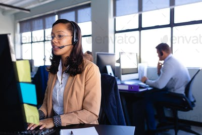 African American woman working with headset phone in office