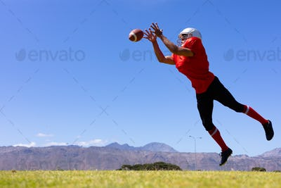 Mixed race male American football player  jumping in the air to catch a football
