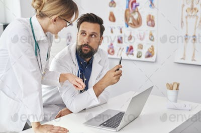Two busy doctors over the laptop