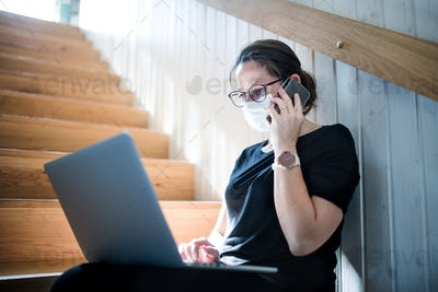 Woman working indoors at home office, Corona virus and quarantine concept