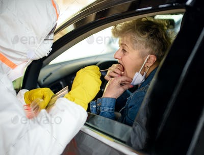 Taking corona virus test sample of senior woman in car, quarantine concept