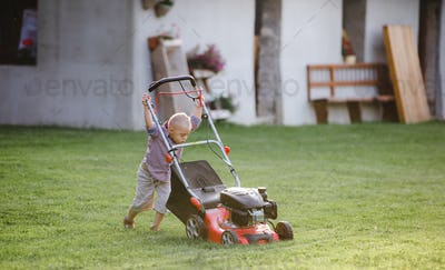 Down syndrome child with lawn mower walking outdoors in garden