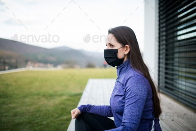 Woman with face masks outdoors at home, Corona virus and quarantine concept