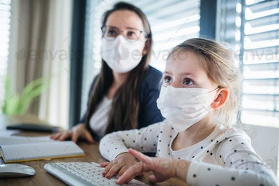 Mother and daughter learning indoors at home, Corona virus and quarantine concept