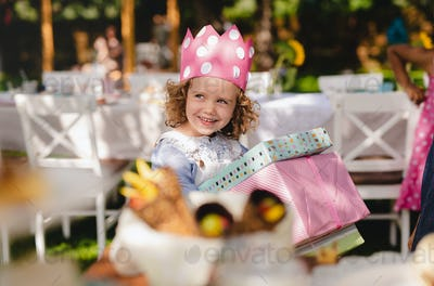 Small girl outdoors in garden in summer, holding presents