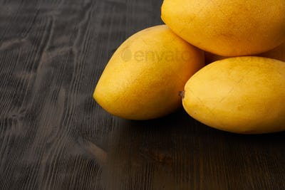 Four whole fruit mangoes on wooden table. Large juicy bright ripe yellow fruits on dark background