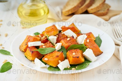 Salad with roasted pumpkin, feta cheese, spinach, nuts with honey and seasonings, side view