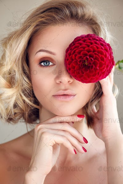 Portrait of a young blonde woman with red flower in hand, hiding eye