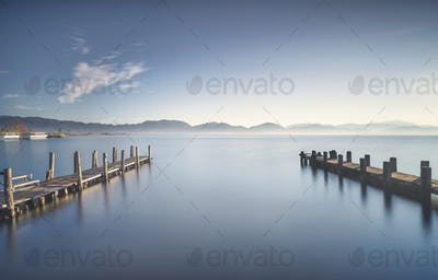 Two Wooden pier or jetty at sunset and sky reflection on water. Versilia Tuscany, Italy