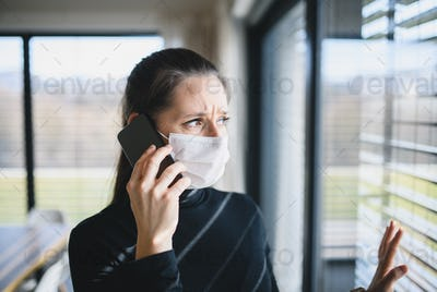 Worried woman with telephone and face masks indoors at home, Corona virus concept