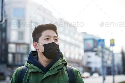 Man wearing face mask in city, coronavirus prevention and protection concept