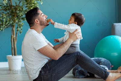 Handsome young father with his baby playing together and having fun at home.