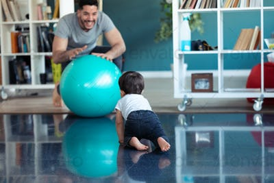 Handsome young father with his baby playing together and having fun with the ball at home.