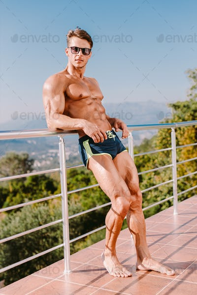 Handsome muscular man posing outdoors shirtless wearing swim trunks and sunglasses