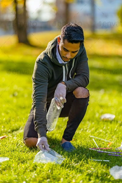 Volunteer cleaning garbage on grass at park