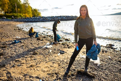 Young woman cleaning beach with volunteers during sunset