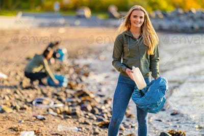 Beautiful Young Volunteer holding bottle and garbage bag at beach