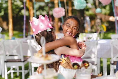Small girls hugging outdoors in garden in summer, birthday celebration concept.