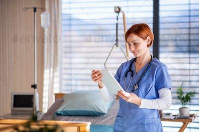 Portrait of female doctor or nurse standing in hospital room, using tablet.