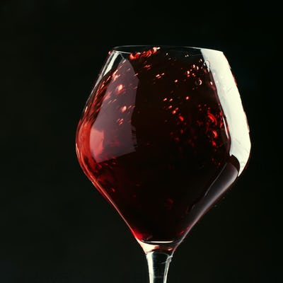 Red wine, splash in a glass, dry cabernet sauvignon, dark background