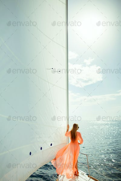 woman in sarong yachting white sails luxury travel